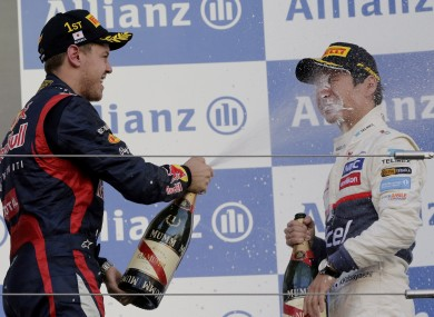 Formula 1 driver Sebastian Vettel, of Germany, sprays champagne into the face of Sauber's Kamui Kobayashi after the 2012 Japanese Grand Prix.