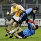 Antrim's Kieran Close with UUJ's Karl McKaigue and Mark Reynolds. Credit: INPHO/Presseye/William Cherry