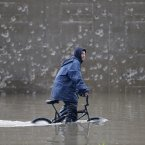 A Lebanese boy, rides his bicycle as he makes his way through a flooded highway, in Beirut, Lebanon. Lebanon has been hit with a snow storm that has blocked roads in the mountains and brought heavy rain showers to the capital Beirut and other coastal areas since Sunday. (AP Photo/Hussein Malla)