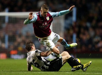 Aston Villa's Joe Bennett (top) is tackled by Newcastle United's Mathieu Debuchy.