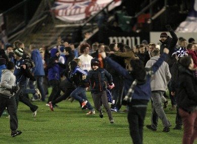 Oldham Athletic fans invade the pitch after the final whistle as they celebrate victory over Liverpool.