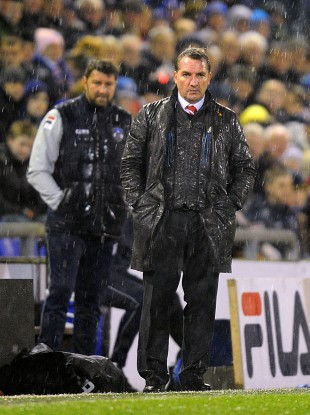 Liverpool manager Brendan Rodgers stands in the rain on the touchline.