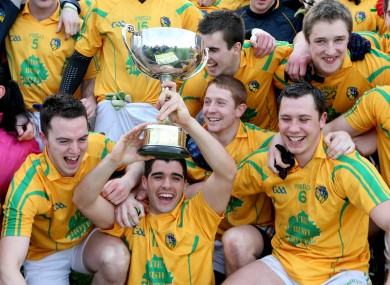The Leitrim team celebrate as captain Emlyn Mulligan holds the trophy.