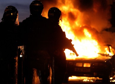 Riot police stand next to a burned out car after Loyalist protesters attacked police lines, in east Belfast.