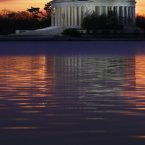The sun rises behind the Jefferson Memorial in Washington on a cloudy day in Washington. A winter weather advisory has been issued for the area with light snow excepted later in the evening. (AP Photo/J. David Ake)