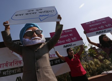 A man wearing a mask of Indian Prime Minister Manmohan Singh, left, participates in a protest along with women outside the court in New Delhi, India