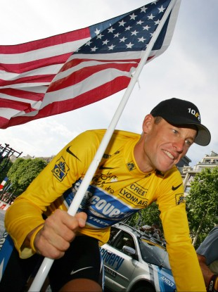 Armstrong carries the US flag during a Tour de France victory parade. (file photo)