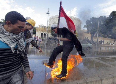 An Egyptian protester tries to escape from fire after he burned an anti-Mohammed Morsi banner in front of the presidential palace in Cairo.