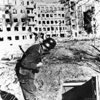 A Nazi solder peers into the entrance of an underground shelter in ruined Stalingrad, Russian, in 1942 during World War II. Bombing and bombardment have made a wreck of the building in the background. (AP Photo)