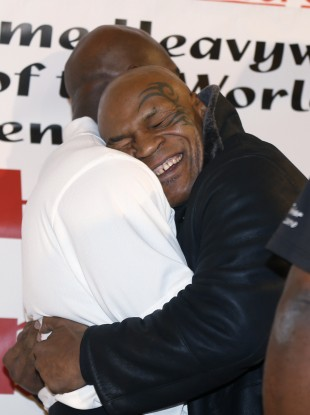 Former heavyweight champion Mike Tyson hugs fellow former champion Evander Holyfield during a promotional event for Holyfield's Real Deal barbecue sauce at a Chicago grocery store yesterday.