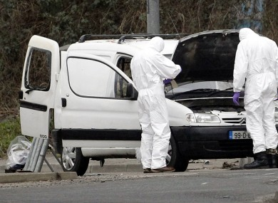 Police forensic officers examine a car in which four mortar rounds were found in Derry