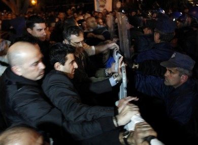 Employees of Laiki Bank, left, push barriers as riot police try to stop them during an anti-bailout protest outside the Cypriot parliament in Nicosia, Cyprus