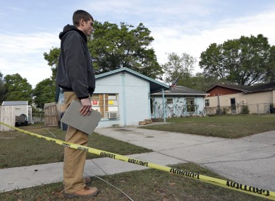An engineer stands in front of a home where sinkhole opened up